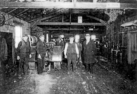 Historic image of people standing around a big machine in Snow Hill.
