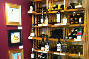 Picture of wine bottles on shelves in the Bishop\'s Stock gallery with paintings displayed on the side.