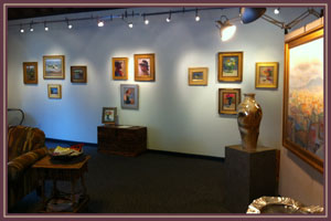 Interior photograph of one of Bishop's Stock gallery wall with an elegant display of paintings and sculpture.