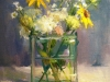 Still life painting of a bunch of wild flowers in a glass vase. The artist is Leslie Belloso and the piece is named Roadside Beauties.